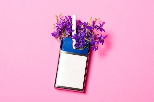 Un pacchetto di sigarette su uno sfondo rosa in un pacchetto di fiori blu