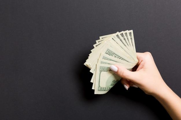 Un pacco di cento banconote in dollari in mano femminile su colorato. concetto di stipendio con spazio di copia