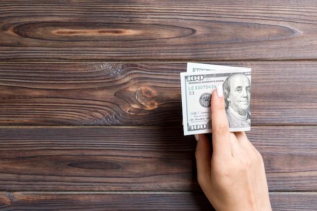 Un pacco di cento banconote in dollari in mano femminile su legno. concetto di stipendio con spazio di copia