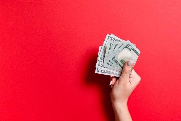 Un pacco di cento banconote in dollari in mano femminile su sfondo colful. concetto di stipendio con spazio di copia