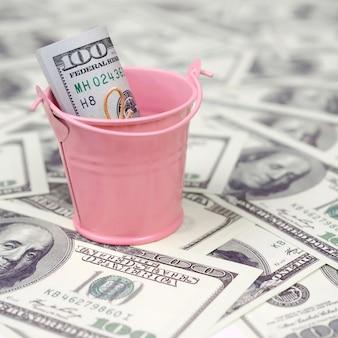 Un pacco di dollari americani in un secchio di metallo rosa su un insieme di banconote da un dollaro