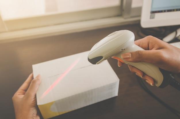 Un pacco di mano umana con lettore di codici a barre per la consegna.