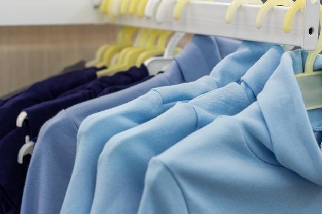 Un pacco di vestiti appesi sugli scaffali dei negozi. concetto di vendita al dettaglio.