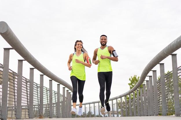 Un paio di atleti formati da una donna bianca e un uomo di colore corrono nel parco ascoltando musica