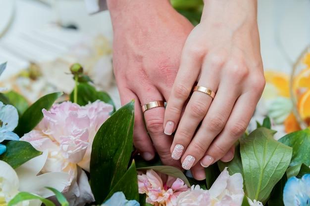 Un paio di fedi in oro sulle mani di una sposa e dello sposo. avvicinamento.