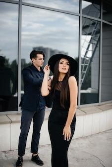 Un paio di giovani belli ed eleganti in abiti neri e occhiali stanno sullo sfondo di un edificio per uffici al tramonto. moda e stile