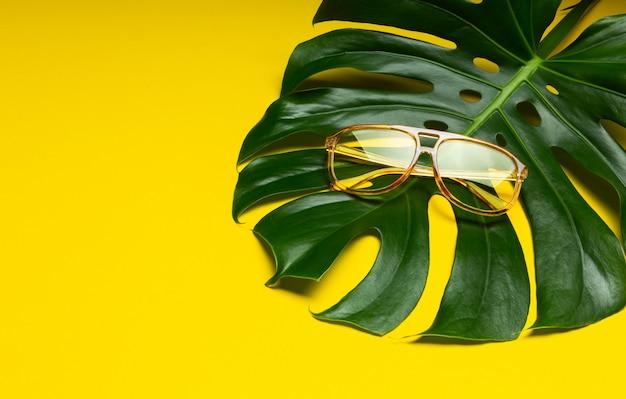 Un paio di occhiali da sole femminili alla moda su verde fresco monstera tropicale foglia isolato su sfondo giallo brillante astratto