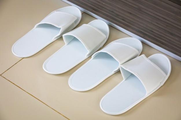 Un paio di pantofole bianche sul pavimento dell'hotel