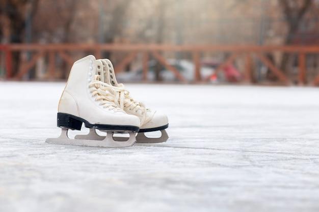 Un paio di pattini bianchi sono in piedi su una pista di pattinaggio aperta. sport invernali