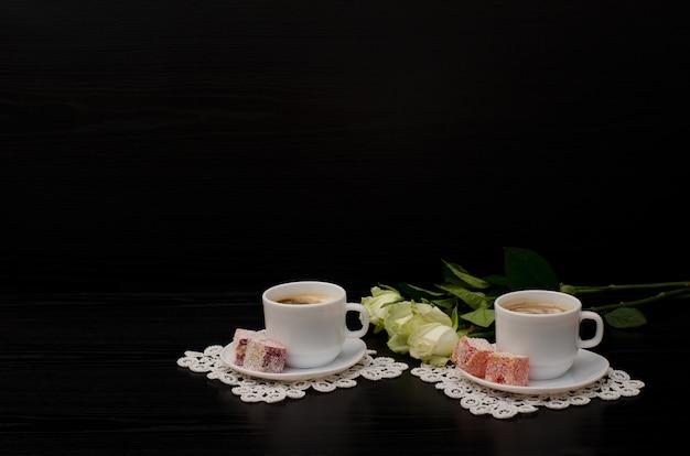 Un paio di tazze di caffè con latte, turkish delight, un bouquet di rose bianche su sfondo nero. spazio per il testo