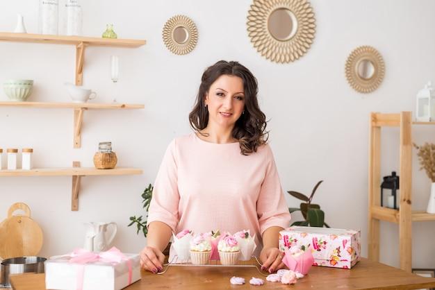 Un pasticcere di donna a casa in cucina ha preparato cupcakes. cupcakes fatti in casa con panna