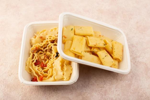 Un pasto della pasta di vista frontale e pasta italiana con i pomodori e la carne all'interno delle ciotole bianche sul colore rosa