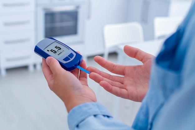 Un paziente diabetico misura la glicemia con un glucometro a casa. la donna che ha il diabete, controlla il livello di glucosio nel sangue