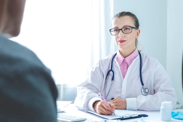 Un paziente riceve una dottoressa nell'ufficio della clinica.