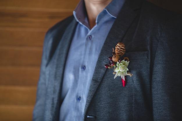 Un perno decorativo di fiori bianchi e frutti autunnali nella giacca di un uomo.