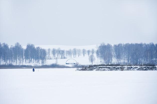 Un pescatore solitario sta pescando in inverno su un lago
