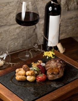 Un pezzo di bistecca con pomodori grigliati rotondi e un bicchiere di vino rosso