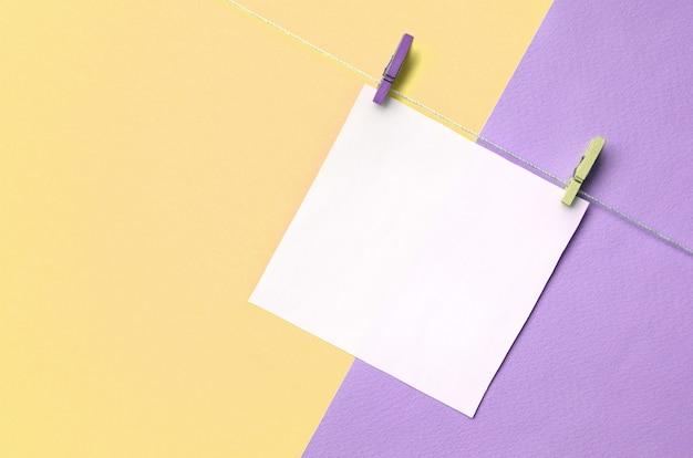 Un pezzo di carta è appeso a una corda con pioli sulla trama di moda colori pastello gialli e viola