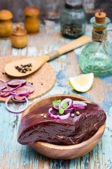 Un pezzo di fegato di manzo crudo in una ciotola e spezie per cucinare su un tavolo di legno