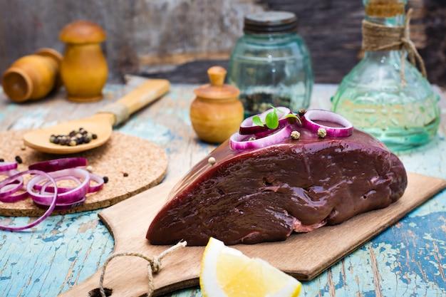 Un pezzo di fegato di manzo crudo su un tagliere, cipolla, limone e spezie per cucinare