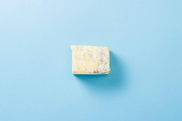Un pezzo di formaggio blu su una superficie blu. minimalismo. vista piana, vista dall'alto.