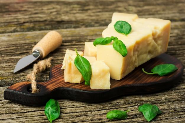 Un pezzo di parmigiano con foglie di basilico e coltello da formaggio su una tavola di legno