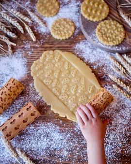 Un pezzo di pasta con una stampa di auto per bambini. mattarelle in legno per biscotti