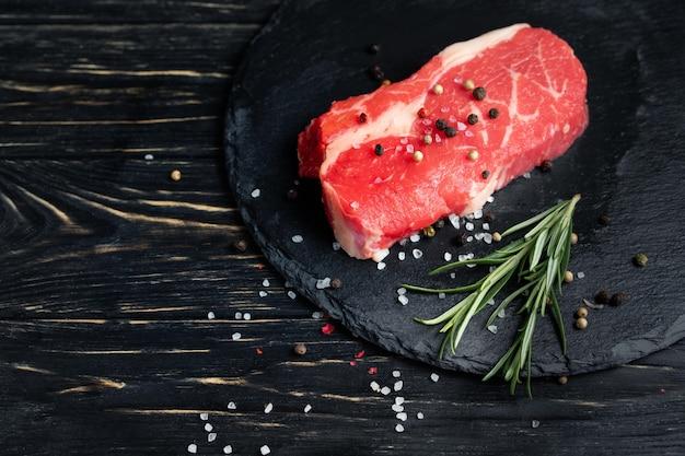 Un pezzo di succosa carne di manzo cruda su un tagliere di pietra su uno sfondo di tavolo in legno nero.