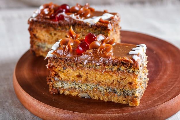 Un pezzo di torta con crema al caramello e semi di papavero su una tavola di cucina in legno, sfondo bianco.
