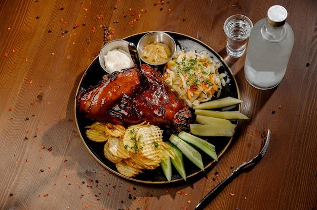 Un pezzo succoso di carne fritta giace su un tagliere contro un tavolo di legno. grado di tostatura ben fatto. concetto di cibo con copia spazio