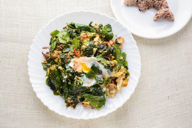 Un piatto bianco di deliziose foglie di baegu fritto o melinjo con uova, servito con riso al vapore,