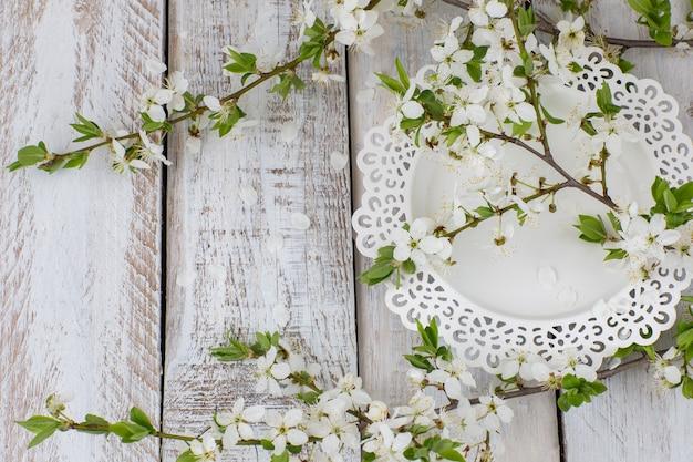 Un piatto bianco e un ramo di fiori di ciliegio