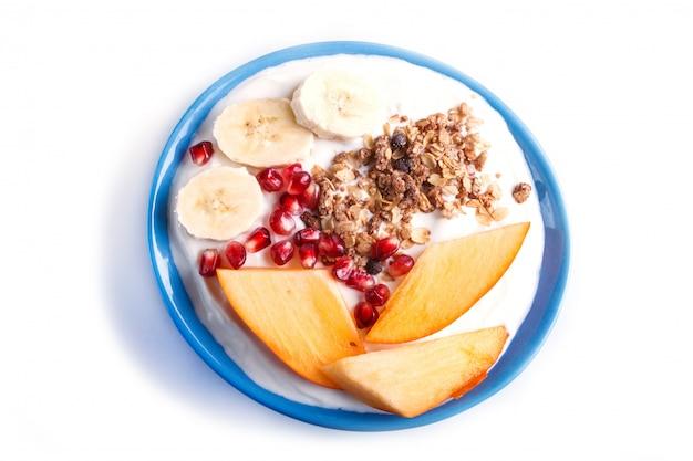 Un piatto blu con yogurt greco, muesli, cachi, banana, melograno isolato su bianco.
