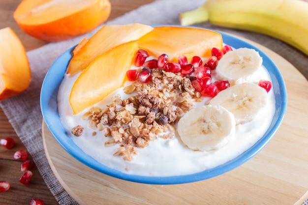 Un piatto blu con yogurt greco, muesli, cachi, banana, melograno su legno marrone.