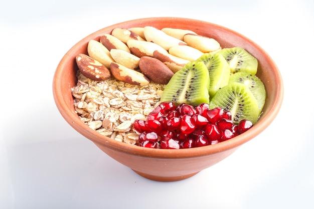 Un piatto con muesli, kiwi, melograno, noci del brasile isolato su sfondo bianco.
