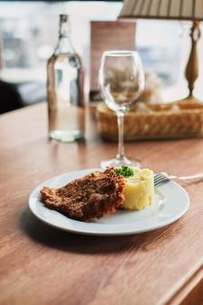Un piatto con purè di patate e un uovo tostato con pomodori e una forchetta.