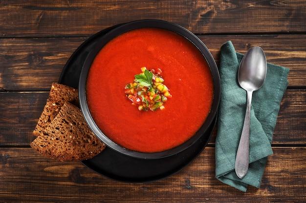 Un piatto con rinfrescante zuppa estiva di gazpacho sulla parete rustica.
