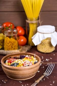 Un piatto di argilla con pasta con basilico, pomodoro e parmigiano