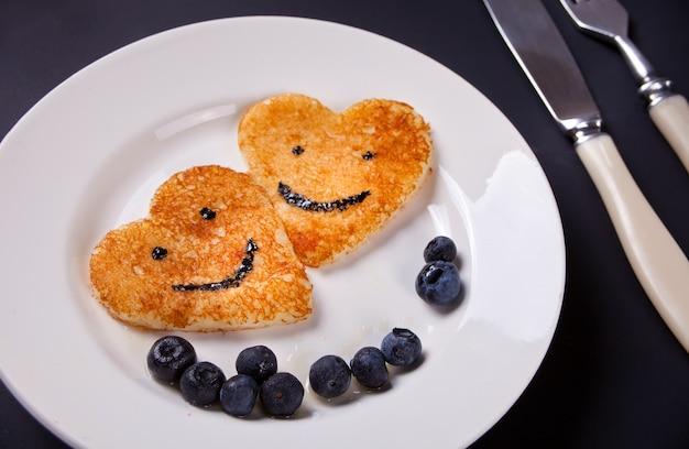 Un piatto di due pancake sotto forma del cuore con le bacche sulla tavola bianca