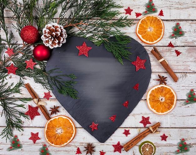 Un piatto di formaggi scuri con copia spazio per il testo in decorazioni natalizie con albero di natale, arancio secco sul vecchio tavolo