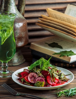 Un piatto di insalata di verdure con un bicchiere di succo verde.