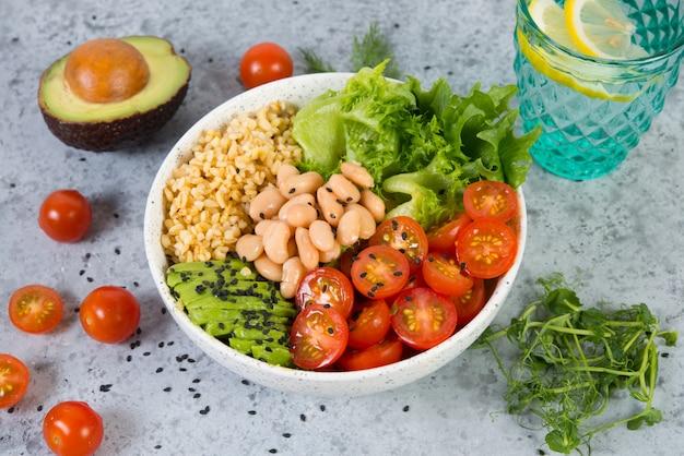 Un piatto di insalata fresca con fagioli bianchi, bulgur, pomodorini e avocado, decorato con semi di sesamo nero con prodotti intorno al piatto. foto orizzontale con copia spazio, vista dall'alto