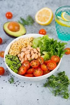 Un piatto di insalata fresca con fagioli bianchi, bulgur, pomodorini e avocado, decorato con semi di sesamo nero con prodotti intorno al piatto.