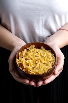 Un piatto di pasta femminile della tenuta di vista frontale con l'italiano della pasta del pasto dell'alimento della pasta italiana
