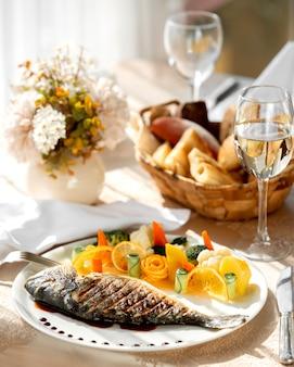 Un piatto di pesce alla griglia servito con verdure bollite e fette d'arancia