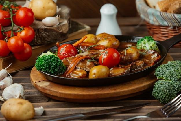 Un piatto di rame nero di cibi grigliati misti e verdure.