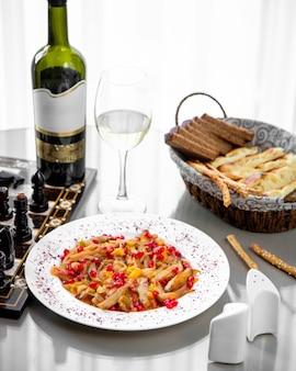 Un piatto di stufato di verdure servito con vino bianco e pane