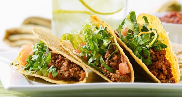 Un piatto di tre tacos su un piatto bianco