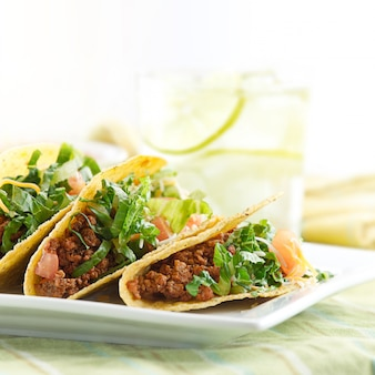 Un piatto di tre tacos sulla piastra bianca