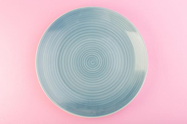 Un piatto di vetro vuoto blu vista dall'alto fatto piatto per pasto sul rosa